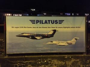 Foto mit Plakatwerbung der Pilatus Flugzeugwerke AG